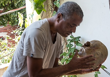 """Marcilio Barroco viser hvordan han bruker leire til å lage """"lesten"""" til ei maske."""